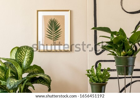 Retro interior design of living room with a lot of plants in green pots, vintage decor, accessoreis and gold mock up picture frame on the beige wall. Minimalistic concept of home decor. Template