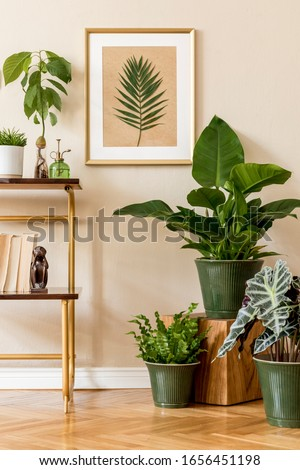 Stylish and retro space of home interior with gold mock up frame, vintage cupboard with accessories and plants composition. Cozy home decor. Home garden. Beige concept of living room. Template.