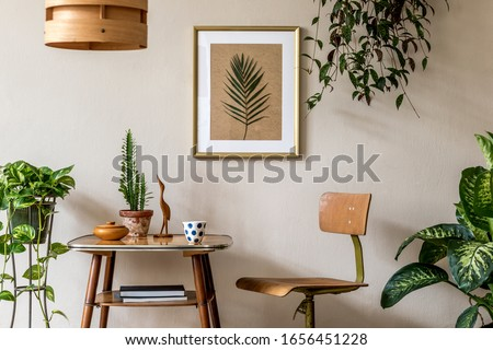 Retro interior design of living room with stylish vintage chair and table, plants, cacti, personal accessories and gold mock up poster frame on the beige wall. Elegant home decor. Template.  Royalty-Free Stock Photo #1656451228