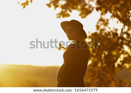 Beautiful pregnant woman in hat and sunglasses outside on warm sunny day. Facing to sun, looks at camera. Summer nature backsides. Yellow tones. Rest in park, meditation, retreat concept #1656471979