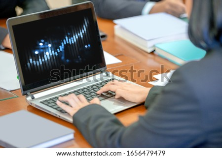 Businesswoman using a laptop with the financial chart in screen on the workplace #1656479479