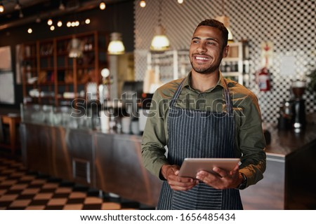 Cheerful young male owner holding digital tablet while standing in cafe Royalty-Free Stock Photo #1656485434