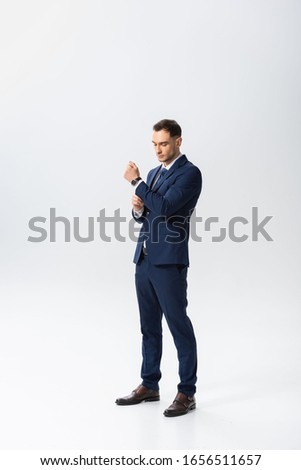 full length view of successful young businessman in blue suit on white background #1656511657