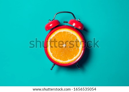 Red alarm clock with orange fruit on the place of watch dial.  #1656535054