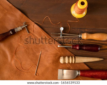 Genuine Leather. Sewing a purse. Leather work. Tools for sewing bags, wallets, clutches. Stitching. Manual sewing of the product. The manufacture of leather products.  #1656539533
