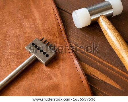 Genuine Leather. Sewing a purse. Leather work. Tools for sewing bags, wallets, clutches. Stitching. Manual sewing of the product. The manufacture of leather products.  #1656539536