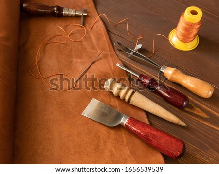 Genuine Leather. Sewing a purse. Leather work. Tools for sewing bags, wallets, clutches. Stitching. Manual sewing of the product. The manufacture of leather products.  #1656539539