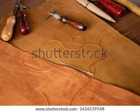 Genuine Leather. Sewing a purse. Leather work. Tools for sewing bags, wallets, clutches. Stitching. Manual sewing of the product. The manufacture of leather products.  #1656539548