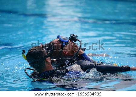 scuba diver show technique help buddy diver accident underwater water in the pool Royalty-Free Stock Photo #1656584935