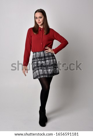 full length portrait of a pretty brunette girl wearing a red shirt and plaid skirt with leggings and boots. Standing pose on a  studio background.