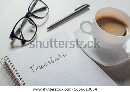close up of coffee and notepad with word translate on workplace