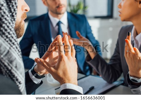 cropped view of multiethnic businesspeople discussing work on meeting with translator in office #1656636001