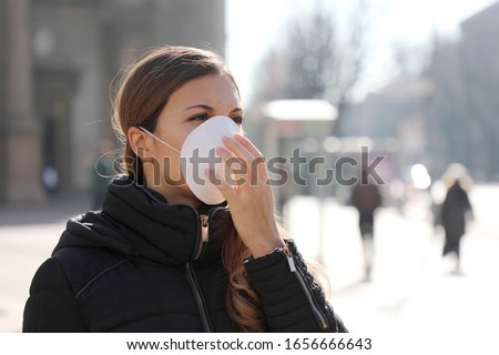 COVID-19 Pandemic Coronavirus Woman in city street wearing face mask protective for spreading of disease virus SARS-CoV-2. Girl with protective mask on face against Coronavirus Disease 2019. #1656666643