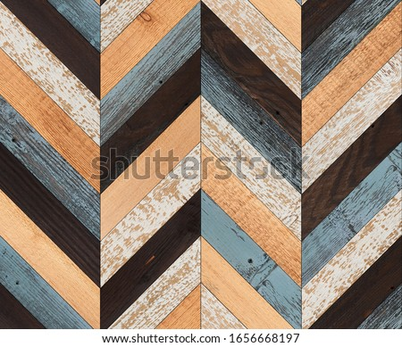 Wooden wall made of painted planks. Wood texture for background. Vintage parquet floor with chevron pattern.