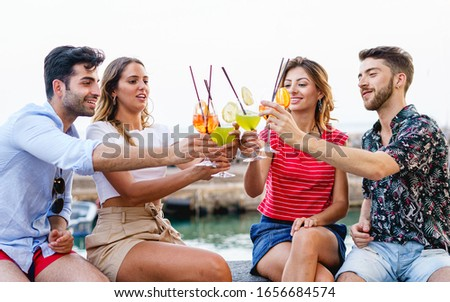 Friends toasting, saying cheers holding tropical blended fruit cocktails. Young people having fun drinking and cheering together lifestyle concept. #1656684574