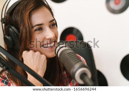 Smiling young woman radio host making podcast recording for online show