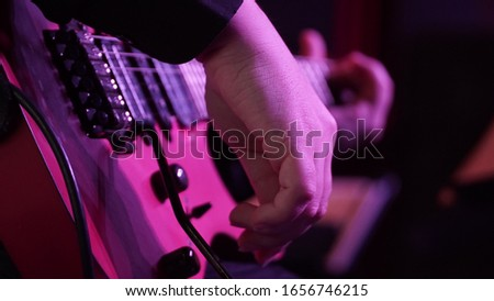 Man playing music with an electro guitar in the concert. Photography of the musician plays the electro guitar. He picks the strings, clamps the strings on the fretboard. High resolution image. #1656746215