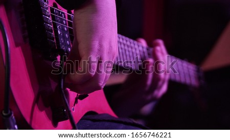 Man playing music with an electro guitar in the concert. Photography of the musician plays the electro guitar. He picks the strings, clamps the strings on the fretboard. High resolution image. #1656746221