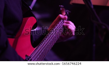 Man playing music with an electro guitar in the concert. Photography of the musician plays the electro guitar. He picks the strings, clamps the strings on the fretboard. High resolution image. #1656746224