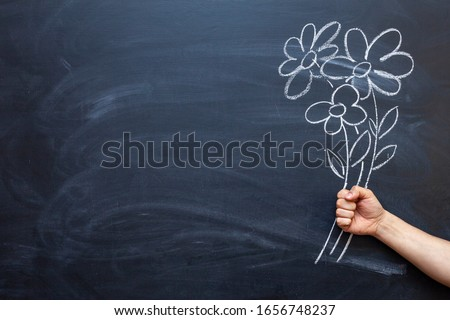 A man's hand holds flowers drawn on a chalkboard in his hand. #1656748237