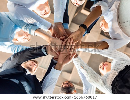 Business Unity And Teambuilding. United Colleagues Standing In Circle Holding Hands Together In Modern Office. Bottom View #1656768817