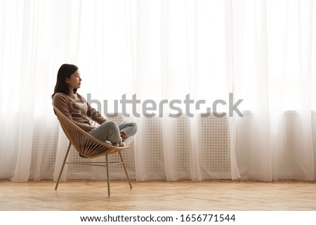 Morning harmony. Girl relaxing in wicker chair and daydreaming against window, side view, copy space #1656771544