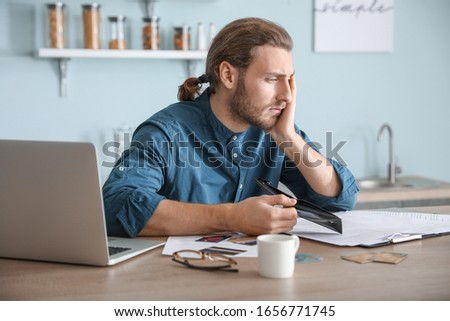 Worried young man in debt at home #1656771745