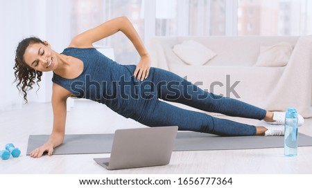 Happy Latin woman doing side plank exercise while watching workout video on laptop at home #1656777364