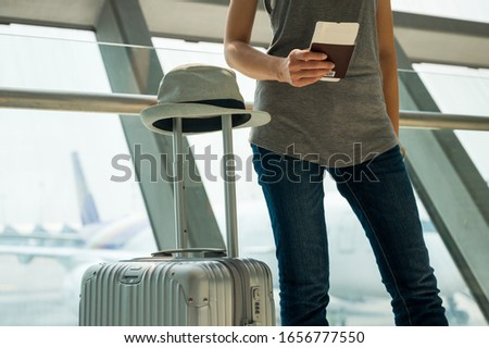 Hand woman holding Passport boarding pass ticket with trolley luggage at airport. Traveler concept #1656777550