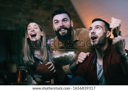 Group of cheerful friends watching sports championship on TV and cheering for their team at home. #1656839317