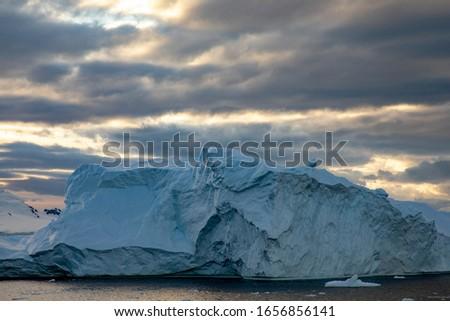 Warm sun rays through cloud cover create beautiful light over iceberg near the South Pole #1656856141