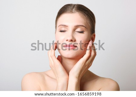Portrait of a beautiful young girl with nude makeup on a light background. The concept of healthy and clean skin, skin care.  #1656859198