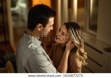 Young loving couple talking while standing face to face at home.