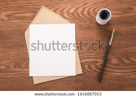 Envelope, ink pen, inkwell on a table	 Royalty-Free Stock Photo #1656887053