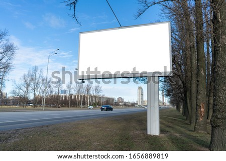 Billboard screen Advertising canvas against the blue sky and trees. Standing near the road with passing cars. With white space for mock-up posters