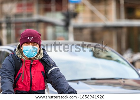 Covid-19 flu disease virus spreading in Europe. People wearing medical mask against corona virus. Healthcare concept. Man riding a bike wearing surgical mask on face in Bucharest, Romania, 2020 #1656941920