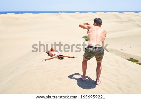 Young beautiful couple making photo at the beach Royalty-Free Stock Photo #1656959221