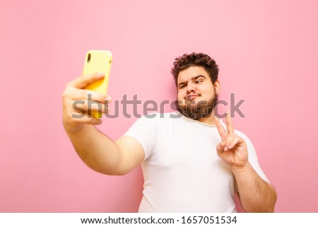 Young man with beard and overweight stands on a pink background, takes a selfie on smartphone camera and shows gesture peace. Funny fat man in white t-shirt makes selfie isolated on pink background