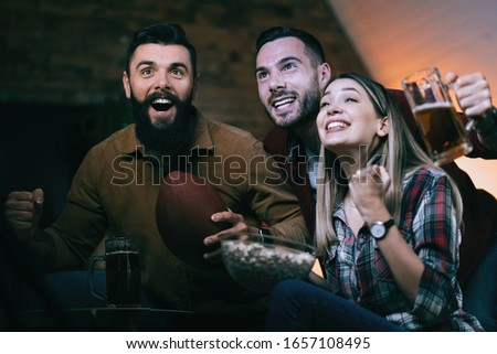 Group of cheerful people watching rugby match on TV and cheering for their team.   #1657108495