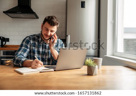 The guy works from home. He sits in the kitchen at the table and uses a laptop computer and speaks on the phone. He is positive, his business is going well. #1657131862