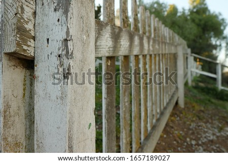 Old weathered white picket fence #1657189027