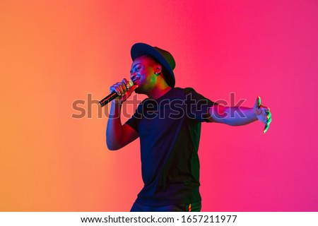 Young african-american musician singing on gradient orange-purple studio background in neon light. Concept of music, hobby, festival. Joyful party host, stand upper. Colorful portrait of artist. Royalty-Free Stock Photo #1657211977