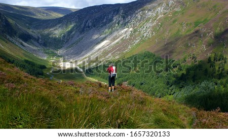 Hiking in Wicklow Mountains National Park, Glendalough, Ireland. Tourist taking a picture in a scenic colorful landscape