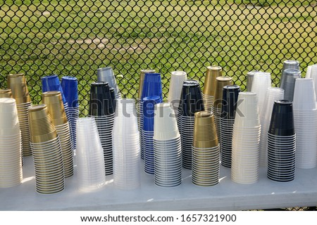 Drink Cups. Various colors of plastic Drink Cups on a table outside. Gold Blue White Black Clear and other Drink Cups. Drink Cups at a Bernie Sanders for President Rally.  #1657321900