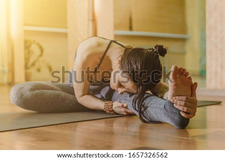 Close-up of a young woman practicing yoga, sitting in head to knee forward exercises, Yana Sirsasana poses, stretching muscles, doing splits #1657326562