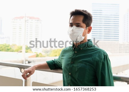A man wearing mask protective for spreading of disease virus Covid-19 and  air smog pollution with PM 2.5 in Bangkok city, Thailand 2020. #1657368253