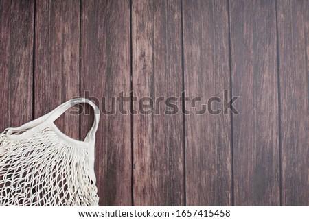 reusable shopping bag on wooden background. Mesh shopping cotton bag. Ecological concept. Ecological concept. Top view #1657415458