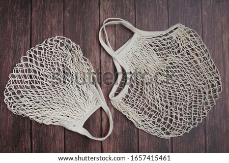 Two reusable shopping bags on wooden background. Mesh shopping cotton bag. Ecological concept. Ecological concept. Top view #1657415461