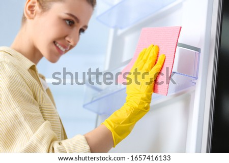 Woman in rubber gloves cleaning empty refrigerator at home, focus on hand with rag #1657416133