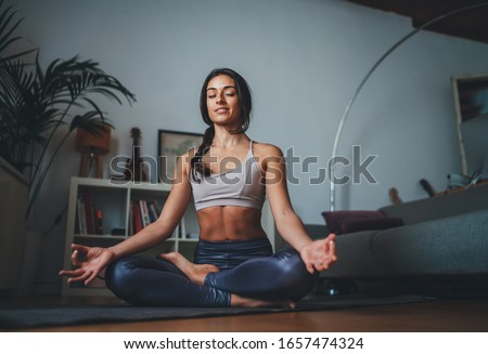 Young healthy beautiful woman in sportive top and leggings practicing yoga at home sitting in lotus pose on yoga mat meditating smiling relaxed with closed eyes, Mindfulness meditation concept #1657474324